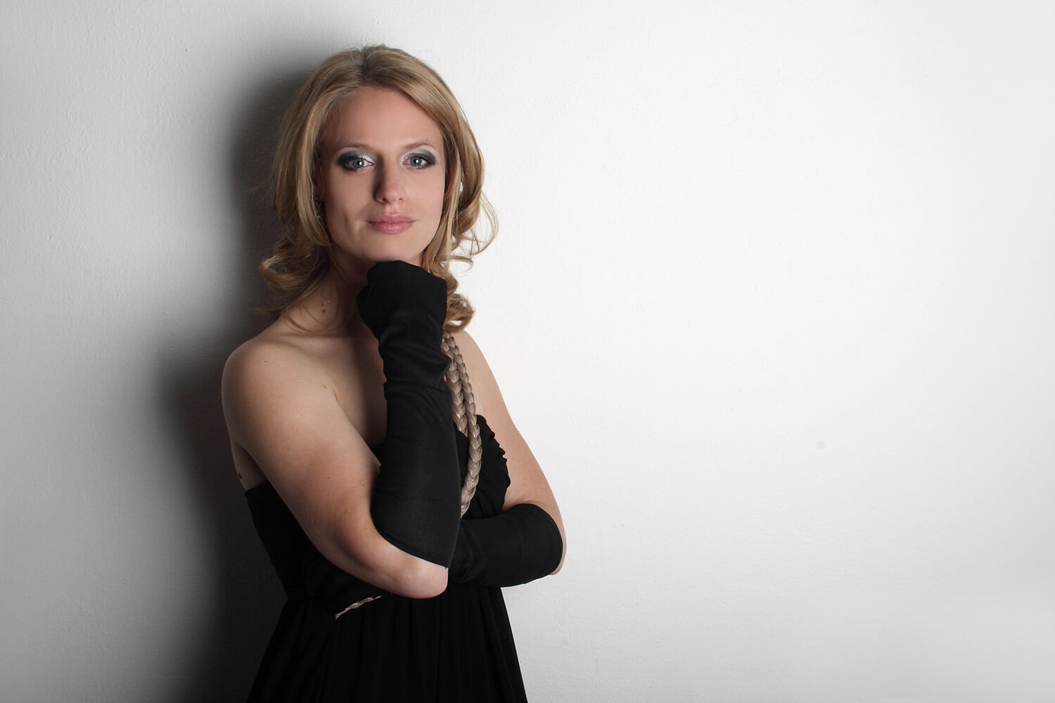 female business portrait in a black dress and gloves on a light background
