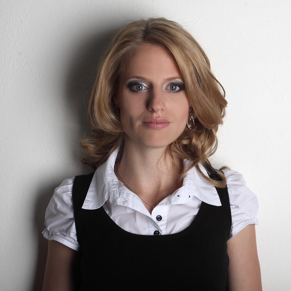 female business portrait in a white shirt and black dress on a light background