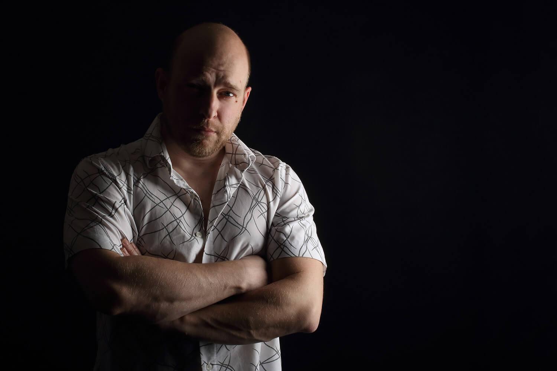 mužský portrét ve světlé košili se založenýma rukama na tmavém pozadí se světlem z boku