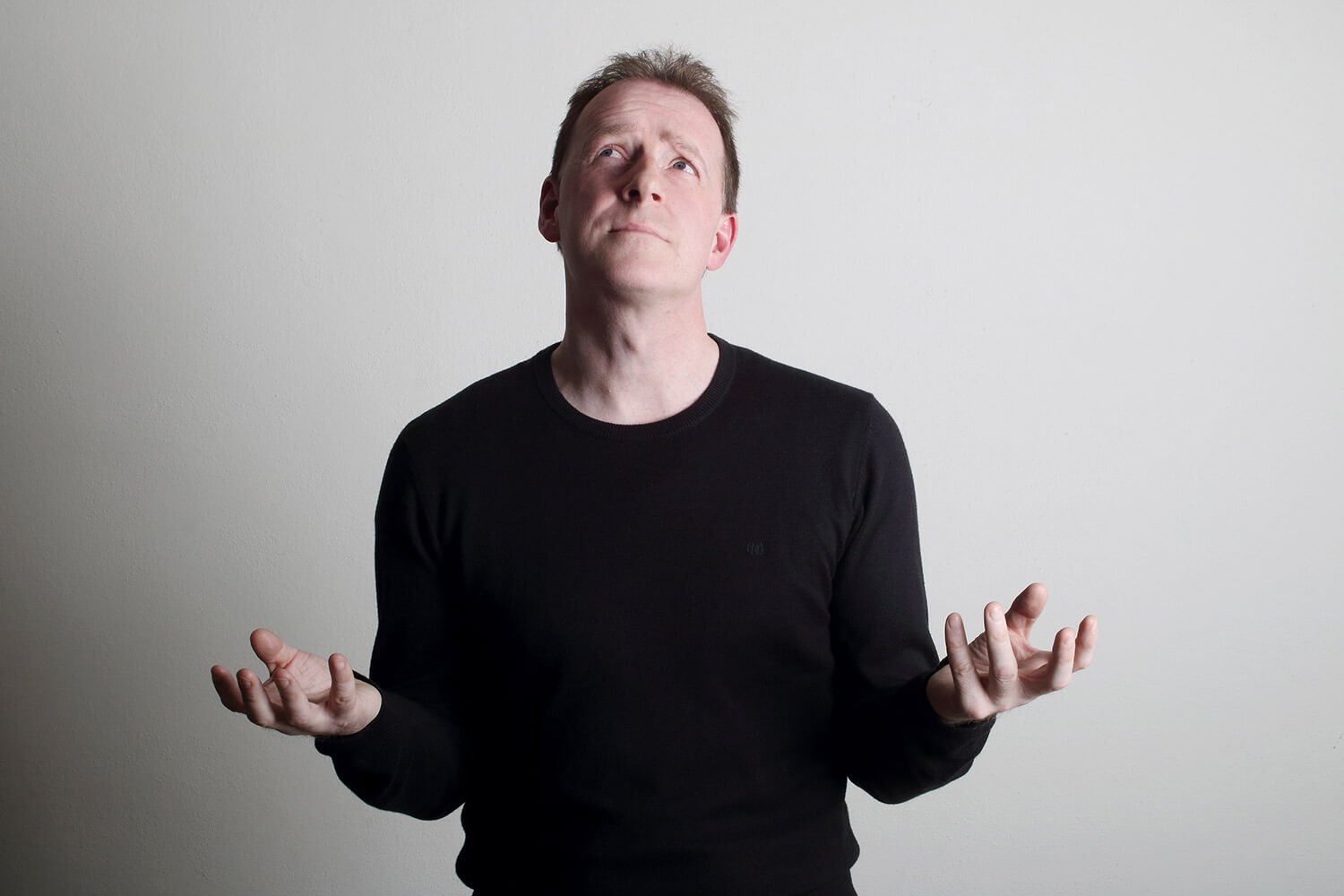 dramatic male portrait in a black T-shirt on a light background