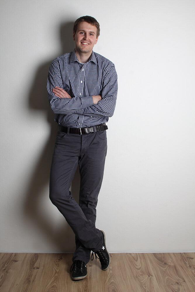 stojící mužský portrét v kostkované košili na světlém pozadí