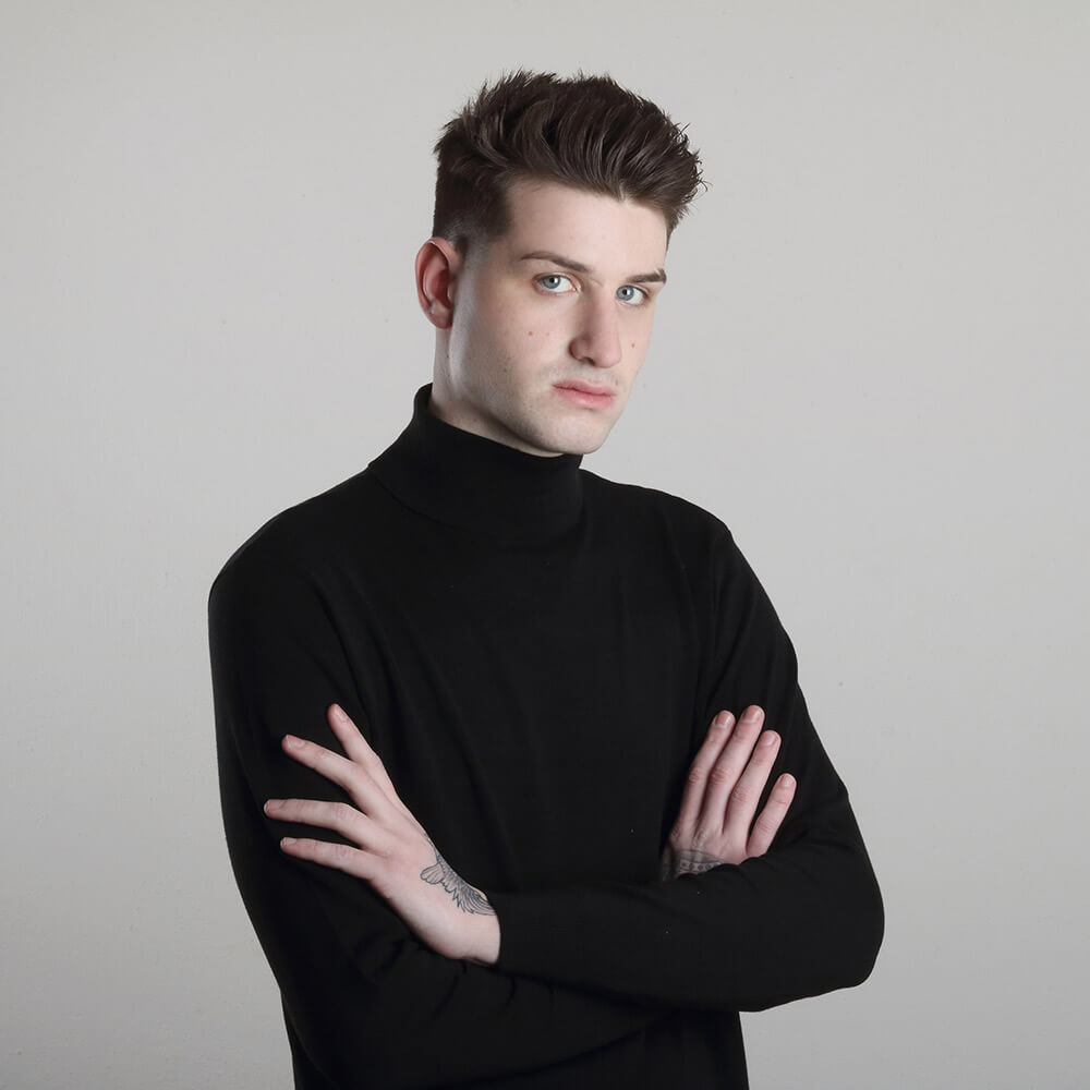 male portrait in a black turtleneck and with a tattoo, on a light background