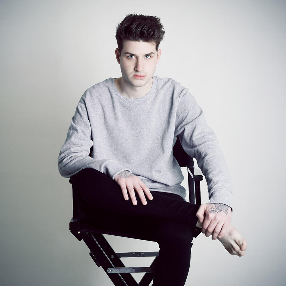 male sitting portrait in a light sweater and dark pants on a light background