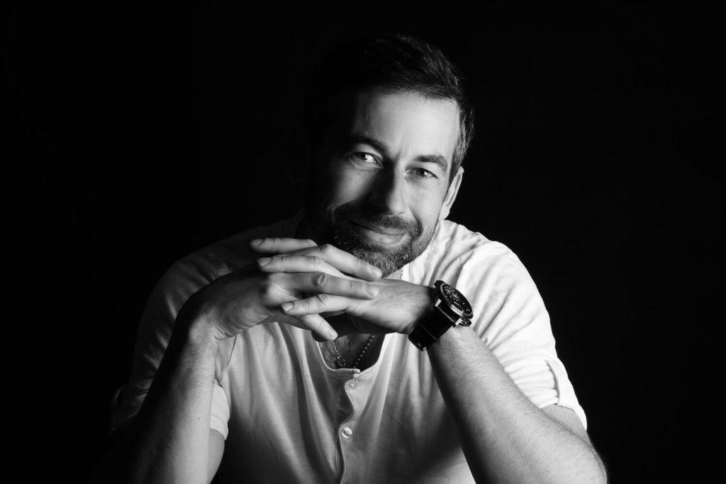 černobílý mužský portrét v bílém triku a s rukama pod bradou na tmavém pozadí