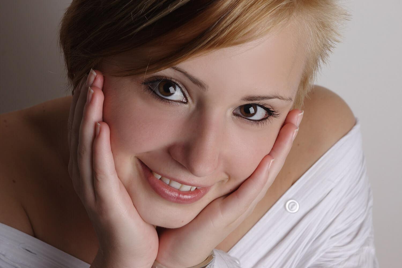 ženský portrét v bílém topu na světlém pozadí