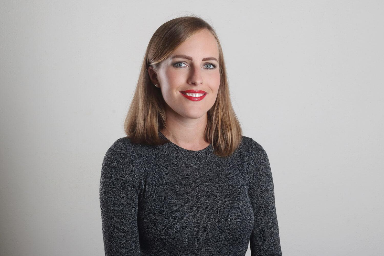ženský portrét v šedém svetru na světlém pozadí