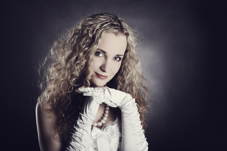 ženský portrét v bílých šatech a rukavicích a s rukama pod bradou na tmavém pozadí