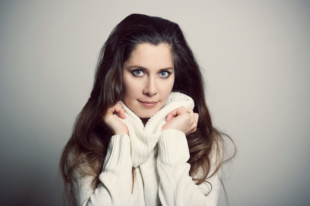 female portrait in a white turtleneck on a light background